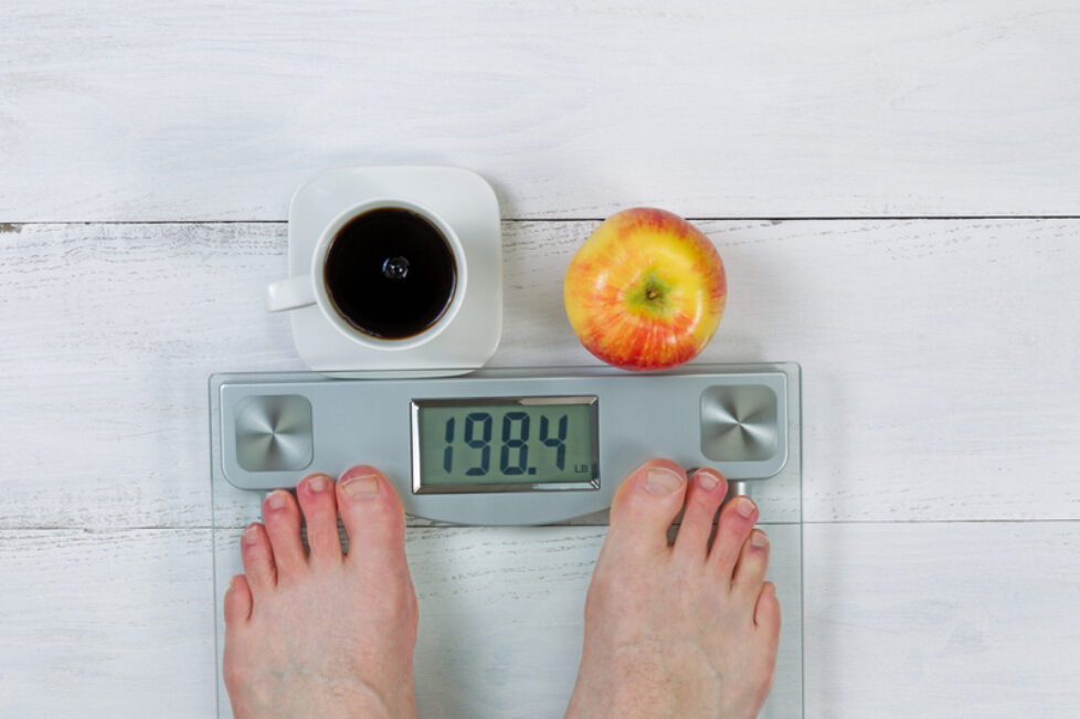 Photo of a weight scale, displaying body weight, with bare male feet and whole apple with black coffee in front on white wooden floor