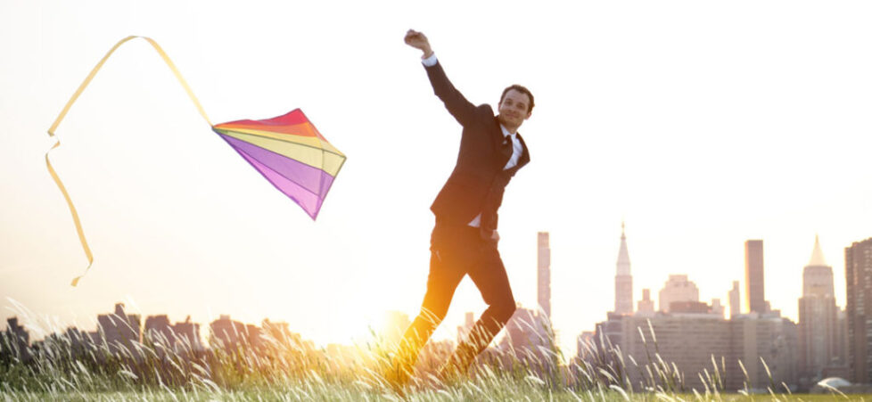 Photo of a businessman flying a kite with a city skyline in the background